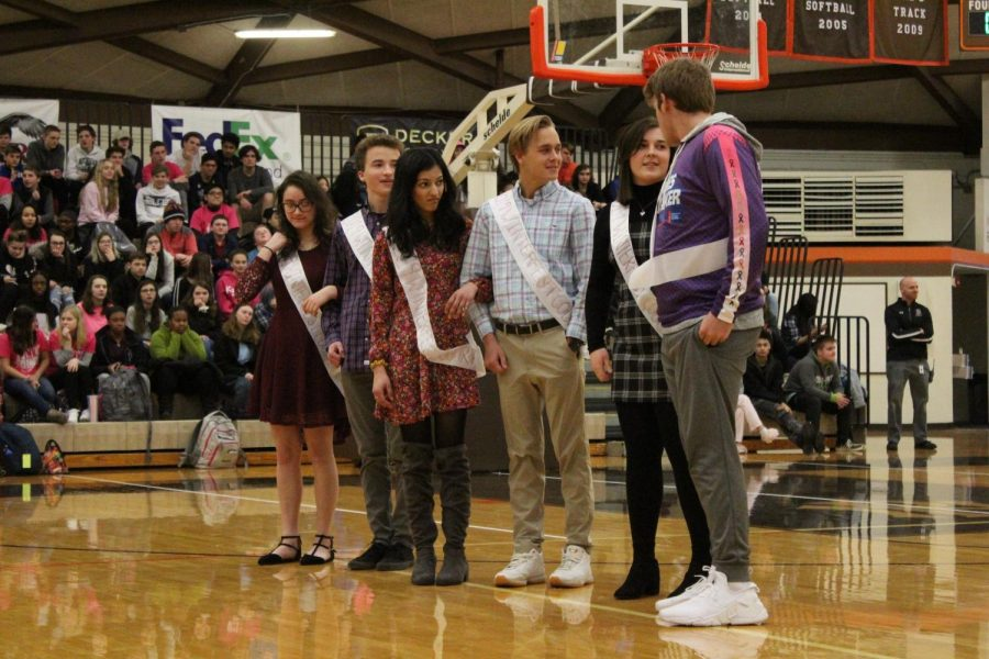 Homecoming court bows as the crowd cheers for them at the pep assembly.