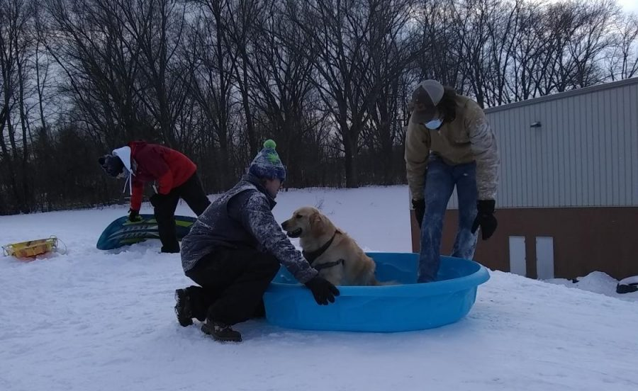 Senior Judson Fargo prepares to ride down Huskie Hill with Hobbs in a plastic kiddie pool. This was just one of many sledding feats attempted by the seniors at WinterFest.