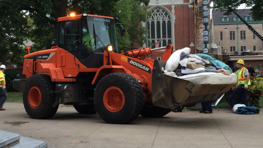 Kalamazoo construction staff sweeping Bronson Part clear of items in the homeless encampment.