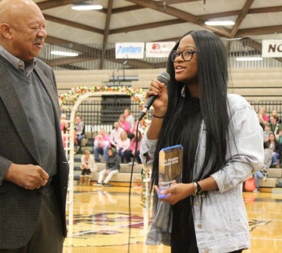 Dr. Houston presents class of 2019 graduate Dorah Stephen with the award named after him at the Winterfest assembly.