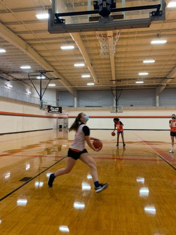 "Freshman Anna Wiltzer eyes a layup at basketball practice. ""I am glad that I have something to look forward to and relieved that I have a place to get rid of energy again,"" she says. All photos by Bryana Quick."